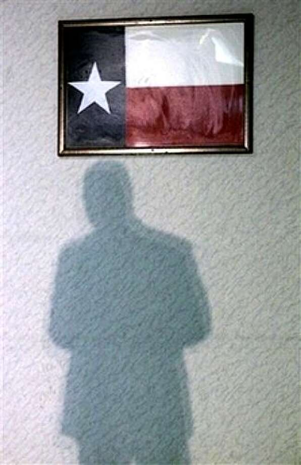 The shadow of a member of  Sen. Barack Obama's, D-Ill., security detail falls on a wall before the Democratic presidential candidate's campaign event at the American Legion Post 490 Friday, Feb. 29, 2008, in Houston, Texas. (AP Photo/Rick Bowmer) Photo: Rick Bowmer, AP / AP