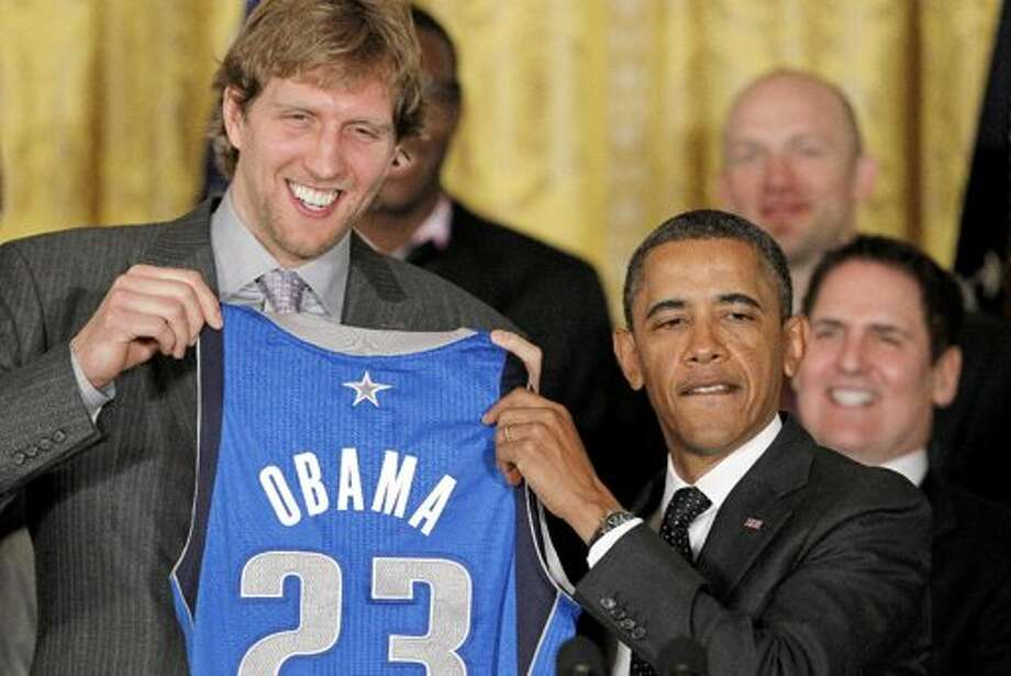 Dirk Nowitzki presents a World Champion Mavs' uniform to President Obama. (Associated Press)