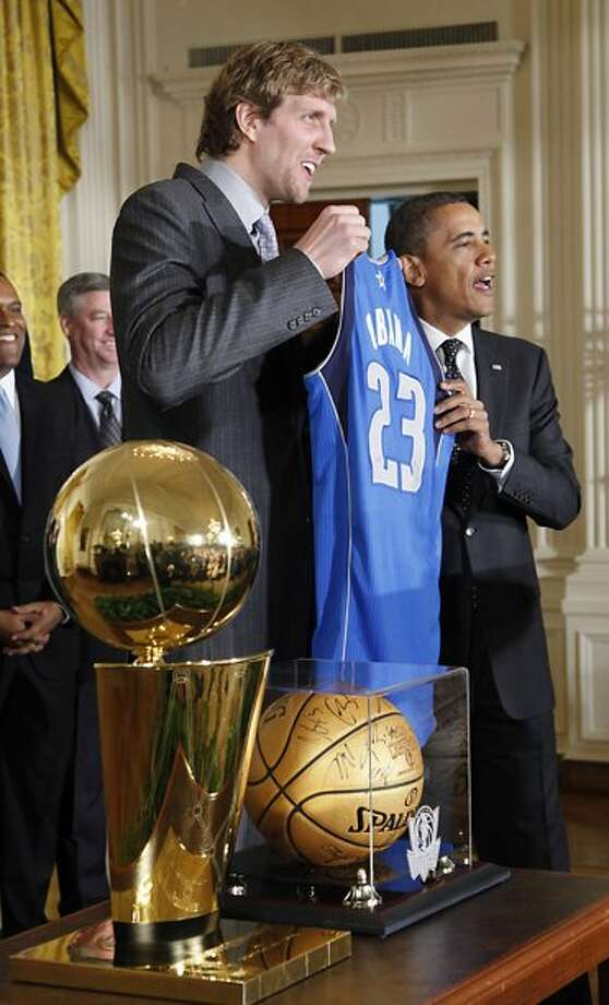 President Obama with the NBA championship trophy won in 2011 by the Dallas Mavericks. (Associated Press)