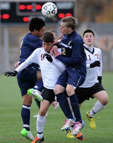 Stamford's Gustavo Torrealba is sandwiched by two Newington players as they all compete for control of the ball during Tuesday's Class LL quarterfinal soccer game at Stamford High School. Photo: Lindsay Niegelberg / Stamford Advocate