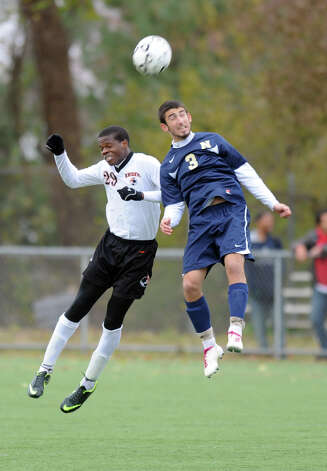 Stamford's Marc Guirand and Newington's Mitchell Ambruso jump to head the ball during Tuesday's Class LL quarterfinal soccer game at Stamford High School. Photo: Lindsay Niegelberg / Stamford Advocate