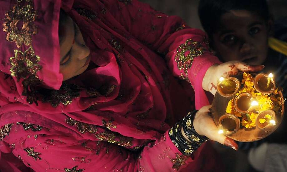 A Pakistani Hindu carries oil lamps on the occasion of Diwali in Lahore on November 13, 2012. People decorate their homes with flowers and Diyas (earthen lamps) to celebrate the homecoming of the God Ram after vanquishing the demon king Ravana and honour the Hindu goddess of wealth, Lakshmi. Photo: Arif Ali, AFP/Getty Images