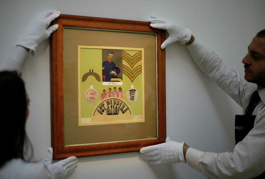 "FILE This Friday, Nov.  9, 2012 file photo shows employees from Sotheby's auction house adjust the original Sir Peter Blake 1967 collage for the iconic Beatles album Sgt Pepper's Lonely Hearts Club Band, which will be sold at  auction, during a press viewing in London. Sotheby's says an original piece of artwork from the Beatles' ""Sgt Pepper's Lonely Hearts Club Band"" album has fetched 55,250 pounds ($87,720) at auction. The auction house said the original 1967 collage for the insert to the album sold to a bidder in London on Tuesday Nov.13, 2012. The sale marked the first time the collage by Sir Peter Blake was on the market.  The auction house said Blake was introduced to the Beatles by his dealer, and that he and his wife worked closely with Paul McCartney and John Lennon to create the imagery of the Sgt. Pepper.  (AP Photo/Alastair Grant, file) Photo: Alastair Grant"