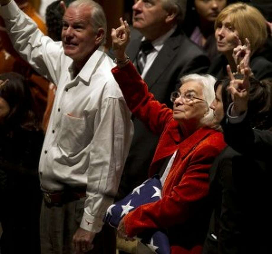 "Edith Royal, wife of Darrell K. Royal, center, holds up the Hook'em Horns as the ""Eyes of Texas"" is played during a public memorial for her late husband on Tuesday in Austin. (Deborah Cannon/Statesman.com)"