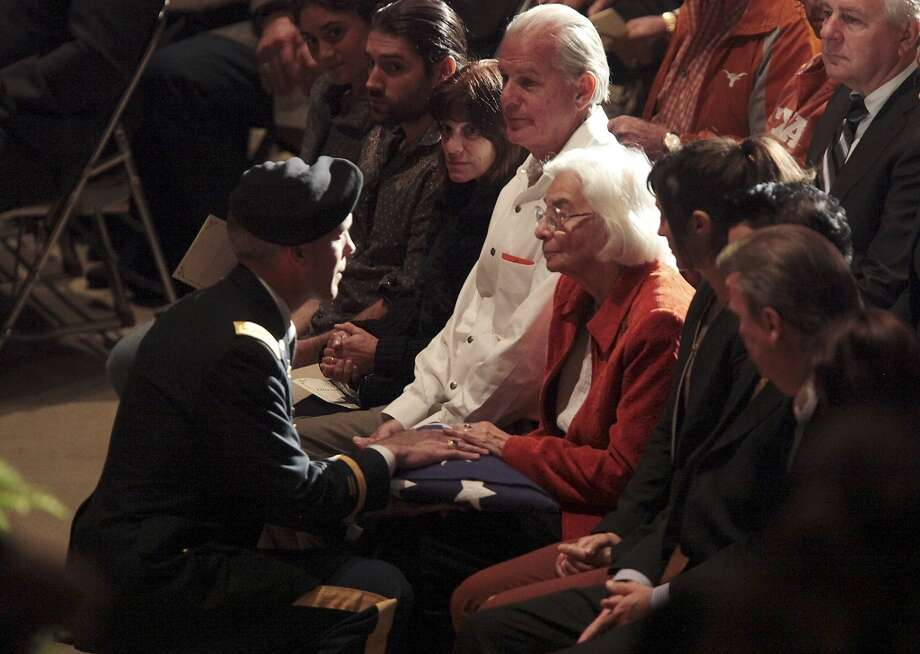 Edith Royal receives the US flag from a member of the University of Texas Army ROTC during a memorial for her husband, former University of Texas Football Coach Darrell K Royal at the Frank Erwin Center in Austin, Tuesday, Nov. 12, 2012. (San Antonio Express-News)