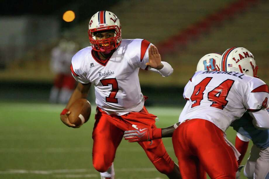 Lamar quarterback Darrell Colbert runs the ball through the backfield as he avoids the Madison defenders Friday night Photo: Matthew White, Freelance / Freelance