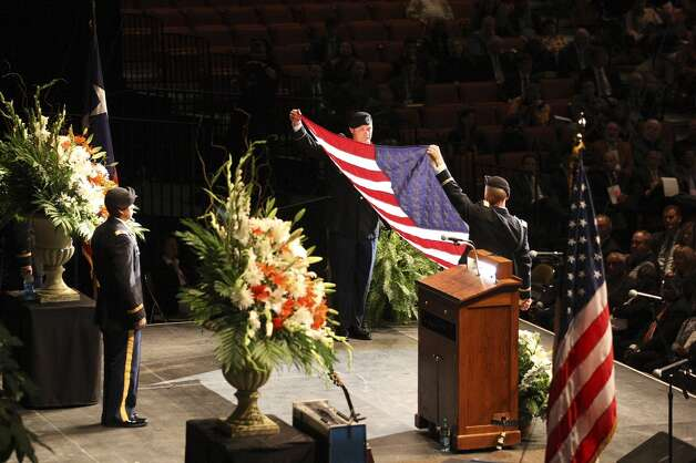 Members of the University of Texas Army ROTC unfurl the flag during the memorial for former University of Texas Football Coach Darrell K Royal at the Frank Erwin Center in Austin, Tuesday, Nov. 12, 2012. (San Antonio Express-News)