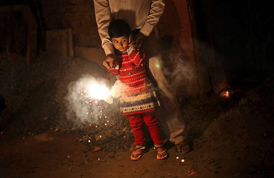 A young Indian girl covers her ear as she is assisted by an adult to play with firecrackers during Diwali celebrations in New Delhi, India, Tuesday, Nov. 13, 2012.  Photo: Altaf Qadri, Associated Press