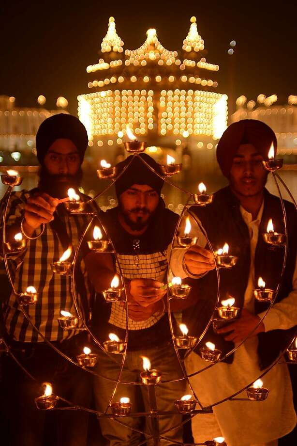 Indian Sikh devotees light oil lamps at the Golden Temple in Amritsar on November 13, 2012, on the ocassion of Bandi Chhor Divas or Diwali. Sikhs celebrate Bandi Chhor Divas or Diwali to mark the return of the Sixth Guru, Guru Hargobind Ji, who was freed from imprisonment and also managed to release 52 political prisoners at the same time from Gwalior fort by Mughal Emperor Jahangir in 1619. Photo: Narinder Nanu, AFP/Getty Images