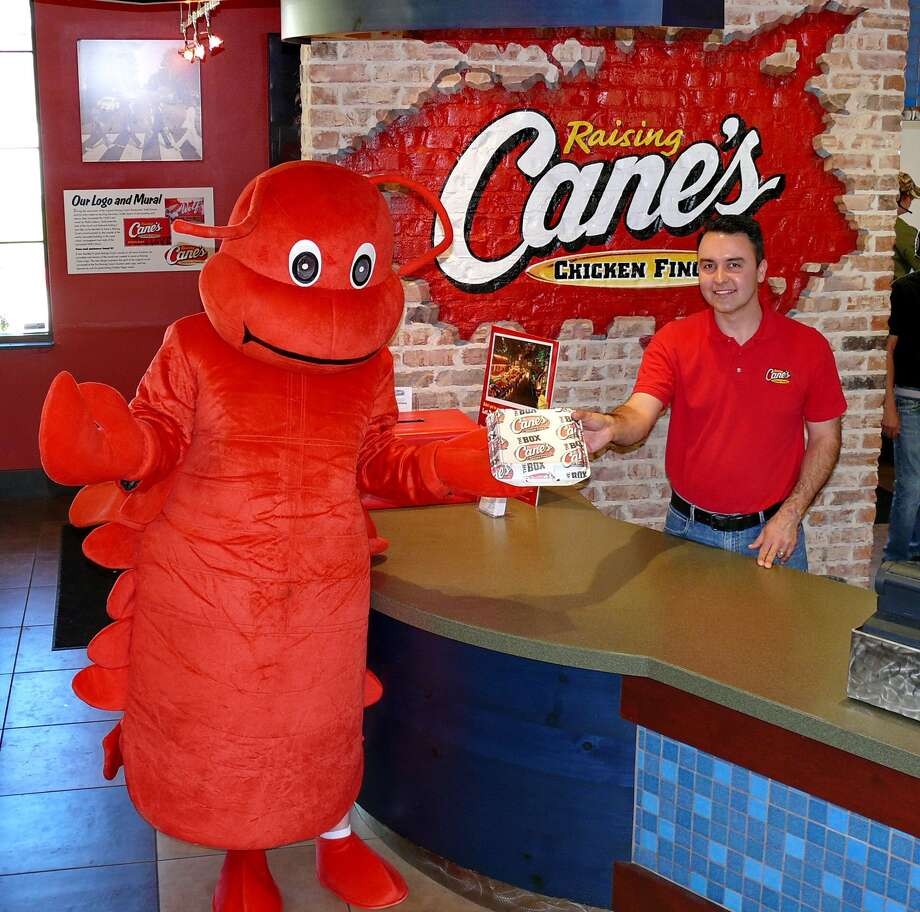 Jesson Gil, owner of Raising Cane's, poses with The Woodlands CrawPHish Festival mascot. Raising Cane's is a proud sponsor of the Festival, which is March 23 at Town Green Park Photo: Contributed Photo