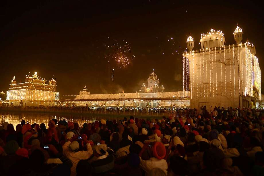 Indian Sikh devotees watch a fireworks display above the Golden Temple in Amritsar on November 13, 2012, on the ocassion of Bandi Chhor Divas or Diwali. Sikhs celebrate Bandi Chhor Divas or Diwali to mark the return of the Sixth Guru, Guru Hargobind Ji, who was freed from imprisonment and also managed to release 52 political prisoners at the same time from Gwalior fort by Mughal Emperor Jahangir in 1619. Photo: Narinder Nanu, AFP/Getty Images