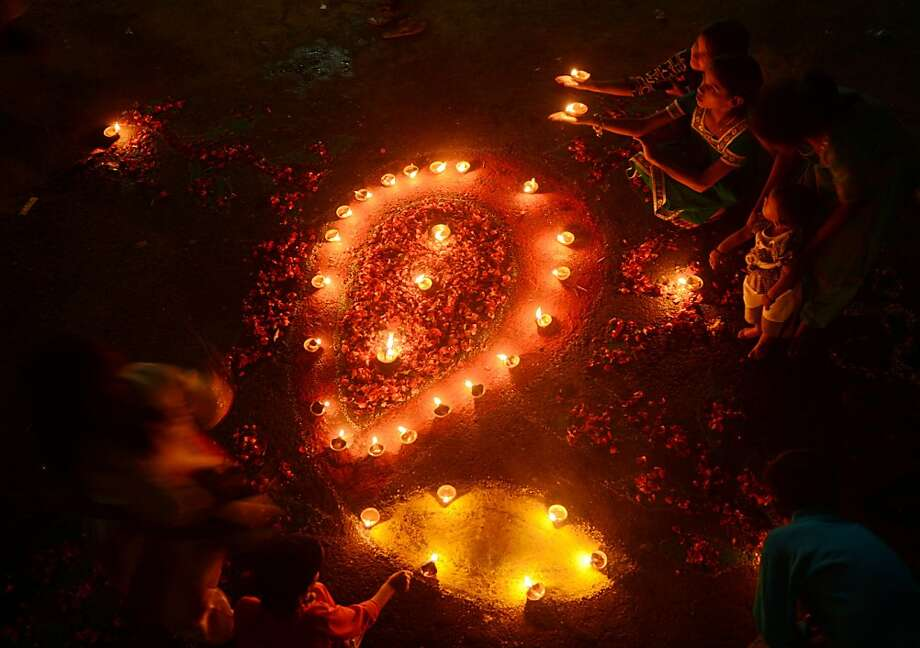 Minority Pakistani Hindu revellers light earthen lamps on the occasion of Diwali in Karachi on November 13, 2012. Diwali, the festival of lights, is celebrated with jubilation and enhusiasm as one of the biggest Hindu festivals. People decorate their homes with flowers and Diyas (earthen lamps), celebrate the homecoming of the God Ram after vanquishing the demon king Ravana and honour the Hindu goddess of wealth, Lakshmi. AFP PHOTO/Asif HASSANASIF HASSAN/AFP/Getty Images Photo: Asif Hassan, AFP/Getty Images