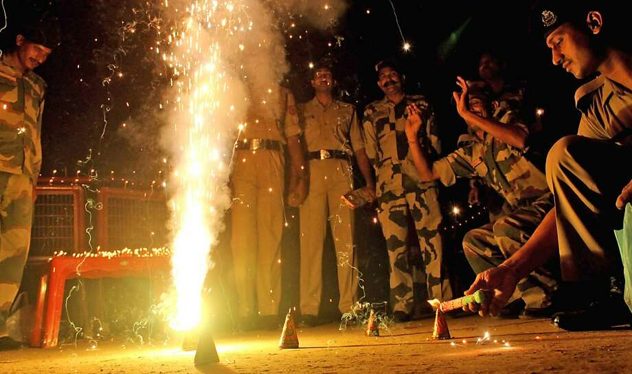 Indian Border Security Force soldiers light candles and crackers as part of Diwali celebrations at the India-Bangladesh border post of Lankamura, about 5 kilometers (3 miles) from Agartala, India, Tuesday, Nov. 13, 2013. Photo: Sushanta Das, Associated Press