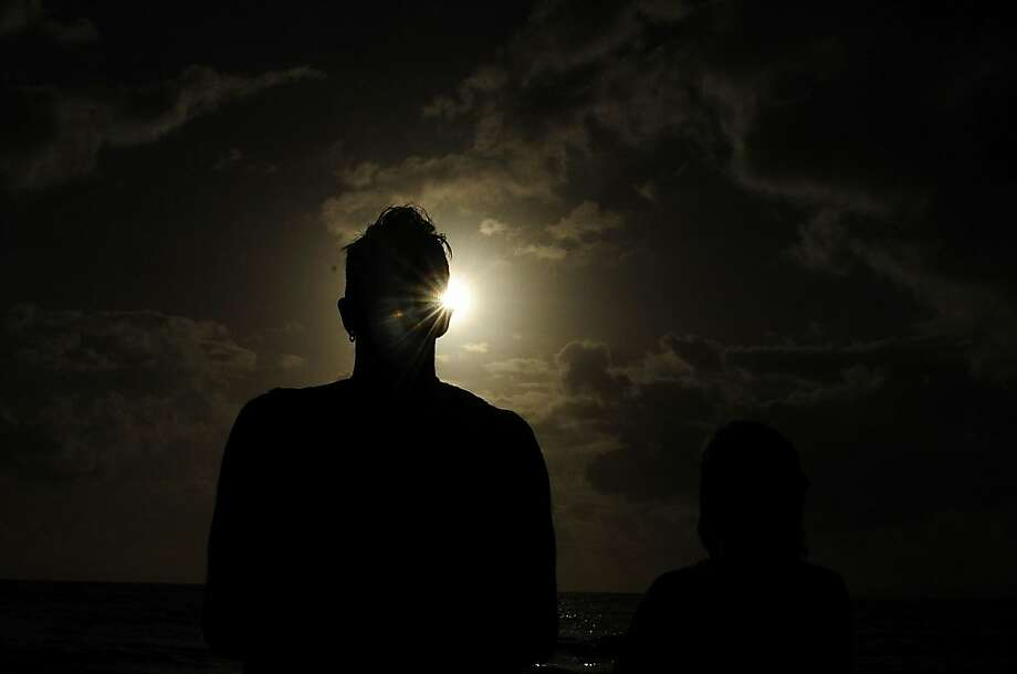 A spectator views the solar eclipse  on November 14, 2012 in Palm Cove, Australia. Thousands of eclipse-watchers have gathered in part of North Queensland to enjoy the solar eclipse, the first in Australia in a decade. Photo: Ian Hitchcock, Getty Images