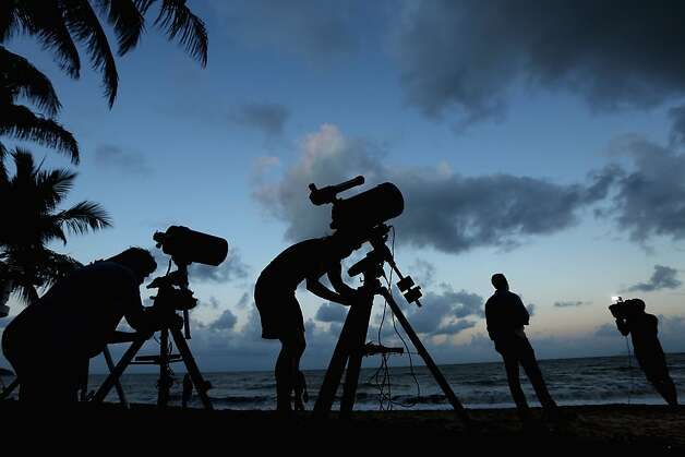 Telescopic cameras and computer equipment are set up on Palm Cove beach in preparation to run a live stream via NASA of the total solar eclipse on November 13, 2012 in Cairns, Australia. Thousands of eclipse-watchers have gathered in part of North Queensland to enjoy the solar eclipse, the first in Australia in a decade. Photo: Mark Kolbe, Getty Images / SF