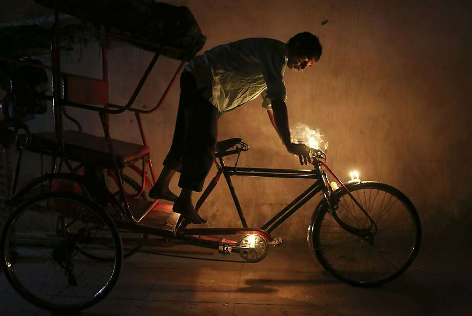 An Indian man stands on his bicycle rickshaw after placing candles on it for good luck and fortune during the festival of Diwali in New Delhi, India, Tuesday, Nov. 13, 2012. Photo: Kevin Frayer, Associated Press