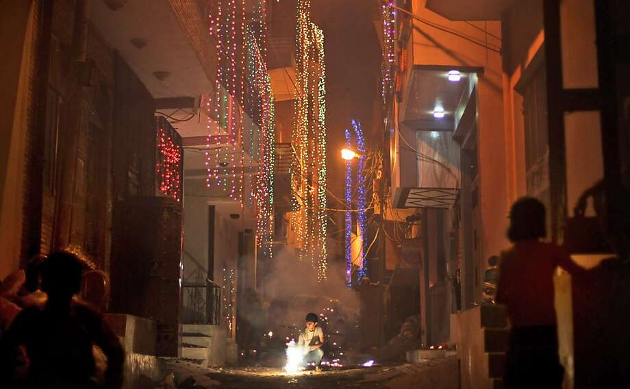 An Indian Hindu boy lights firecrackers in a small alleyway during Diwali celebrations in New Delhi, India, Tuesday, Nov. 13, 2012. Photo: Altaf Qadri, Associated Press