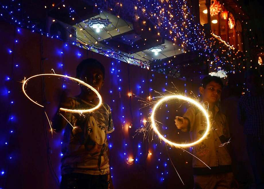 Pakistani Hindu revellers wave sparklers on the occasion of Diwali in Karachi on November 13, 2012. Diwali, the festival of lights, is celebrated with jubilation and enhusiasm as one of the biggest Hindu festivals. People decorate their homes with flowers and Diyas (earthen lamps), celebrate the homecoming of the God Ram after vanquishing the demon king Ravana and honour the Hindu goddess of wealth, Lakshmi. AFP PHOTO/Asif HASSANASIF HASSAN/AFP/Getty Images Photo: Asif Hassan, AFP/Getty Images