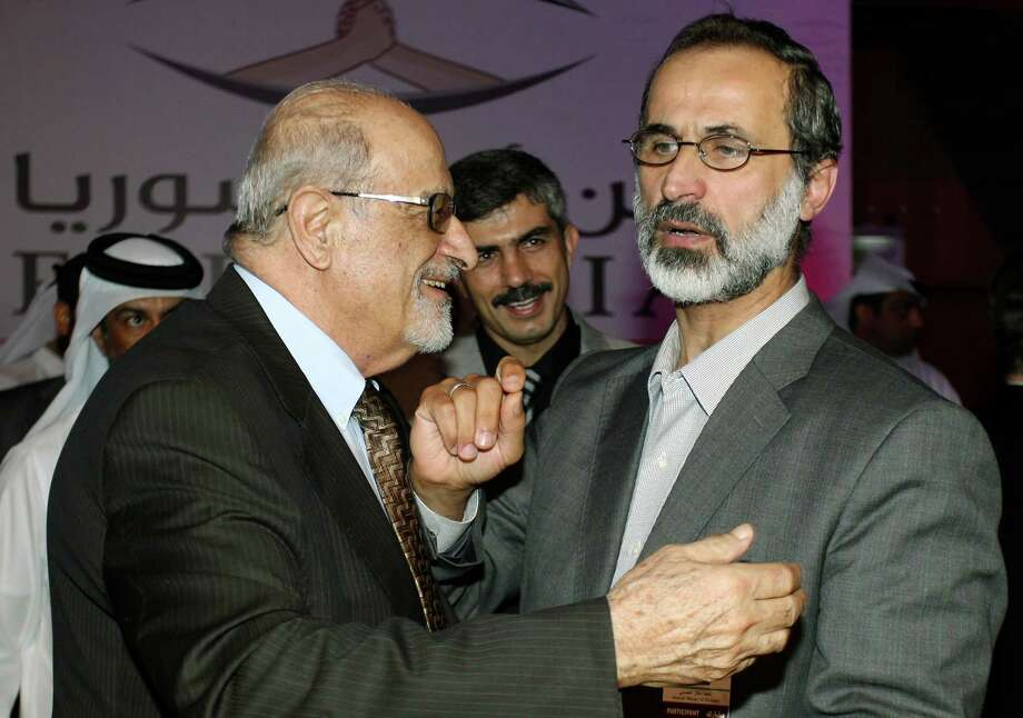 In this Sunday, Nov. 11, 2012 file photo, Syrian opposition figure and prominent Syrian human rights activist Haytham al-Maleh, left, congratulates Muslim cleric Mouaz al-Khatib after he was elected president of the newly formed Syrian National Coalition for Opposition and Revolutionary Forces, in Doha, Qatar. While lacking in political experience, Al-Khatib, the 52-year-old preacher-turned-activist is described by Syrians as a man of the people--a modest, unifying figure who commands wide respect among the country?s various opposition groups and rebels. (AP Photo/Osama Faisal) Photo: Osama Faisal, STR / AP