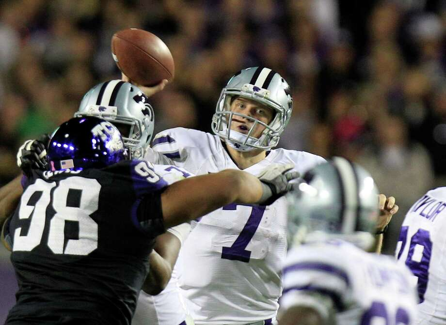Kansas State quarterback Collin Klein (7) passes as teammate offensive linesman Aderius Epps, second from left, blocks TCU defensive tackle Jon Lewis (98) during the first half of an NCAA college football game, Saturday, Nov. 10, 2012, in Fort Worth, Texas. (AP Photo/LM Otero) Photo: LM Otero, Associated Press / AP