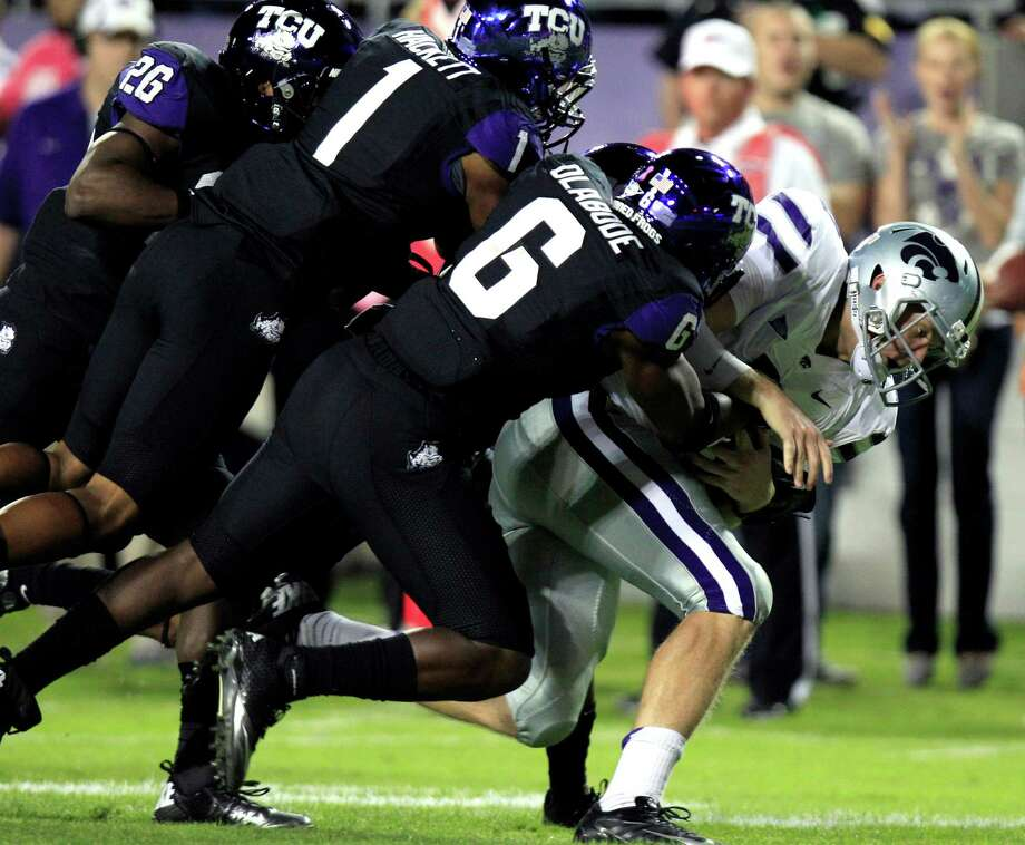 Kansas State quarterback Collin Klein (7) scrambles for the first down on the keeper against TCU defenders David Jenkins (26), Chris Hackett (1) and Elisha Olabode (6) during the first half of an NCAA college football game, Saturday, Nov. 10, 2012, in Fort Worth, Texas. (AP Photo/LM Otero) Photo: LM Otero, Associated Press / AP