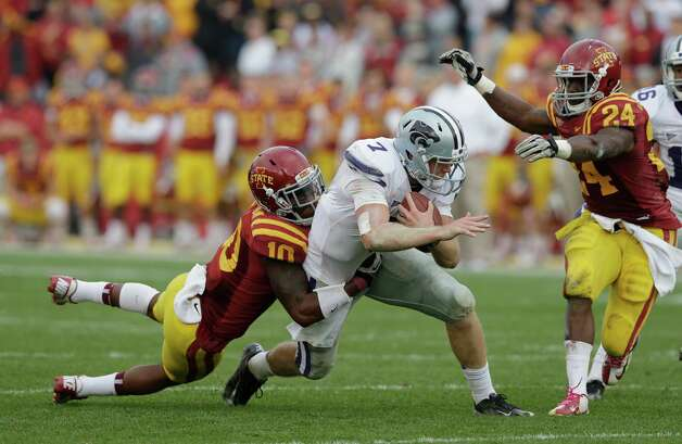 Kansas State quarterback Collin Klein, center, runs between Iowa State defenders Jacques Washington, left, and Durrell Givens, right, during the second half of an NCAA college football game, Saturday, Oct. 13, 2012, in Ames, Iowa. Kansas State won 27-21. (AP Photo/Charlie Neibergall) Photo: Charlie Neibergall, Associated Press / AP