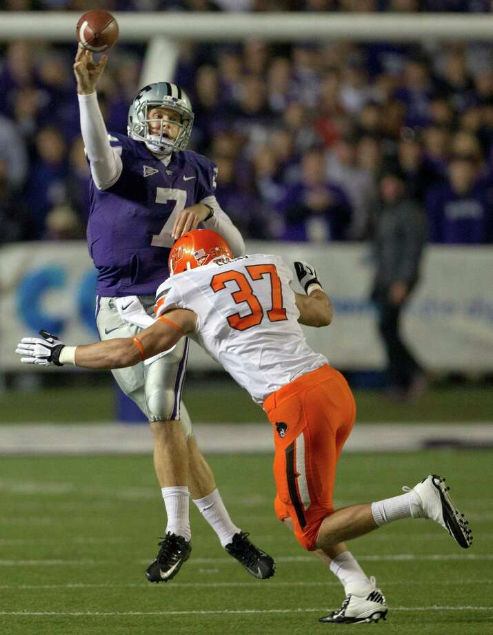 Kansas State quarterback Collin Klein (7) passes over the rush of Oklahoma State linebacker Alex Elkins (37) during the first half of an NCAA college football game in Manhattan, Kan., Saturday, Nov. 3, 2012. (AP Photo/Orlin Wagner) Photo: Orlin Wagner, Associated Press / AP