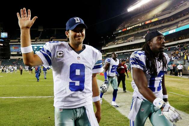 Dallas Cowboys quarterback Tony Romo, left, and wide receiver Dwayne Harris walk off the field after an NFL football game against the Philadelphia Eagles, Sunday, Nov. 11, 2012, in Philadelphia. Dallas won 38-23. (AP Photo/Julio Cortez) Photo: Julio Cortez, Associated Press / AP