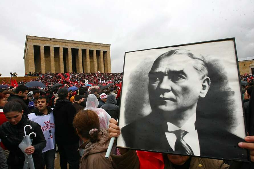 A portrait of Mustafa Kemal Ataturk is held during a tribute in Ankara to the founder of modern Turk