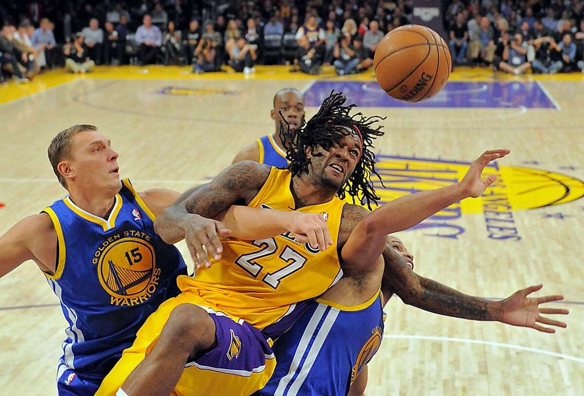 Los Angeles Lakers center Jordan Hill, center, goes after a rebound as Golden State Warriors forward Andris Biedrins of Latvia and forward Richard Jefferson, right, defend during the second half of their NBA basketball game, Friday, Nov. 9, 2012, in Los Angeles. The Lakers won 101-77. (AP Photo/Mark J. Terrill)