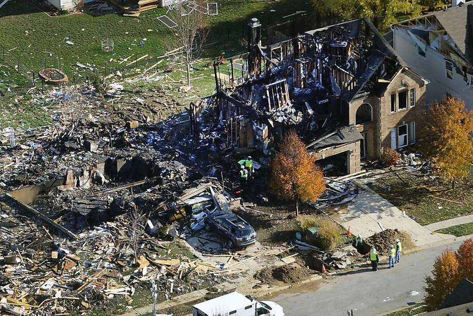 Citizens Energy workers continue their investigation Monday at the site of an explosion that leveled two houses and damaged others in Indianapolis on Saturday. The cause is not yet clear. Photo: Matt Kryger, Associated Press