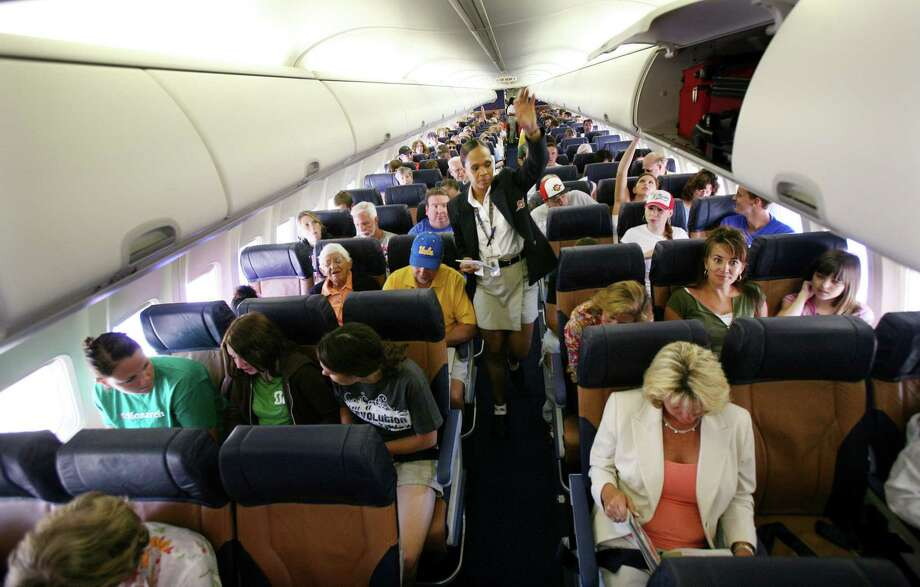 A flight attendant secures an overhead bin as passengers await take-off from San Diego. This year, families might find it costlier to sit together on their Thanksgiving trips. Photo: Sandy Huffaker, Stringer / Getty Images North America