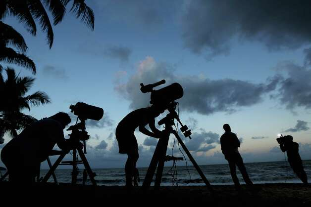 Telescopic cameras and computer equipment are set up on Palm Cove beach in preparation to run a live stream via NASA of the total solar eclipse on November 13, 2012 in Cairns, Australia. Thousands of eclipse-watchers have gathered in part of North Queensland to enjoy the solar eclipse, the first in Australia in a decade. Photo: Mark Kolbe, Getty Images / 2012 Getty Images