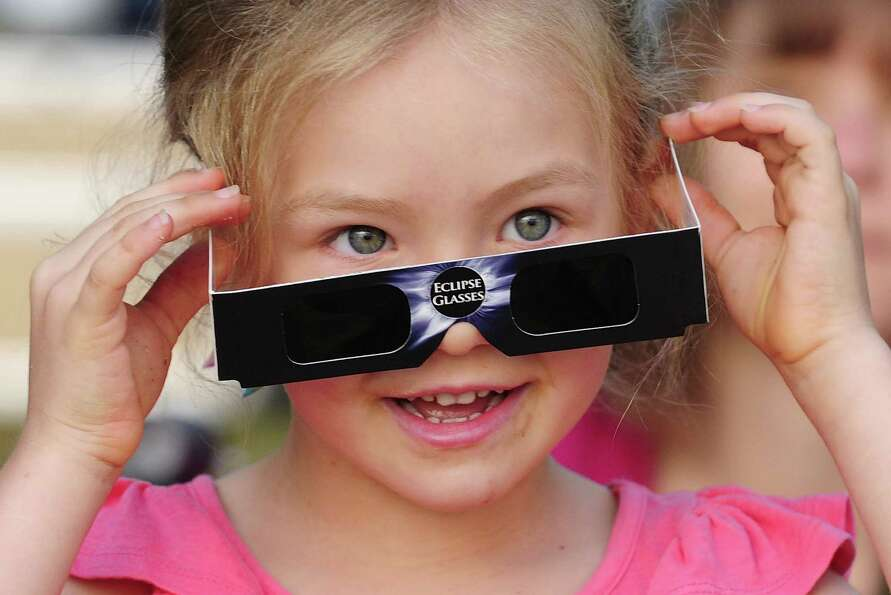 A young girl attempts to view the solar eclipse through special eclipse viewing glasses  on November