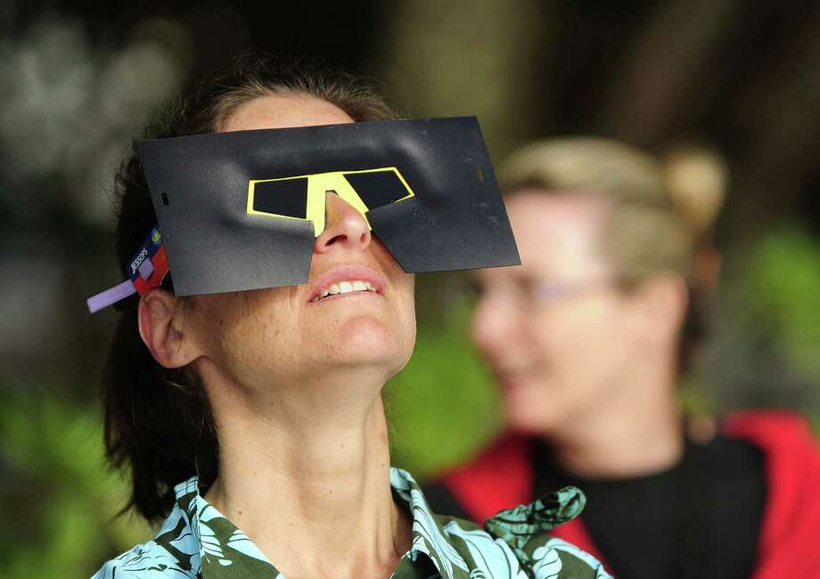A spectator views the solar eclipse through special eclipse viewing glasses  on November 14, 2012 in Palm Cove, Australia. Thousands of eclipse-watchers have gathered in part of North Queensland to enjoy the solar eclipse, the first in Australia in a decade. Photo: Ian Hitchcock, Getty Images / 2012 Getty Images