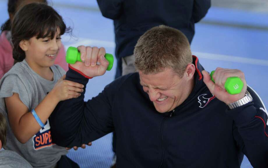 Sarah Gonzalez, 8, a third grader at Briarmeadow Charter School, helps Houston Texans player J.J. Watt as he pretends to struggle with three pound weights during his visit at their school Tuesday, Nov. 13, 2012, in Houston.  The event was part of NFL Super School Visit, an annual program in which a star player from each team visits a school in his community. He spoke about the importance of good health and lead kids in fitness activities, as part of NFL's PLAY 60 campaign, helping kids get 60 minutes of exercise a day. On behalf of the NFL, Watt presented the school with a $10,000 NFL PLAY 60 grant for health and wellness programming or equipment. Photo: Melissa Phillip, Houston Chronicle / © 2012 Houston Chronicle