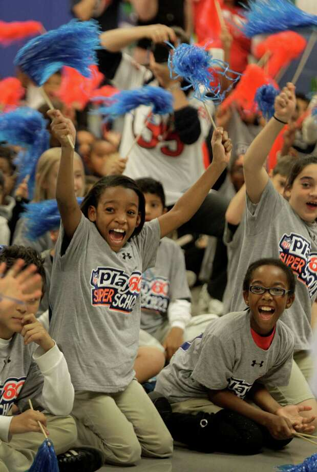 Mikell Thompson, left, and Dorleon Pittman, right, both 9-year-old fourth graders at Briarmeadow Charter School, cheers among their classmates as Houston Texans player J.J. Watt arrives in the auditorium during a visit at their school. Photo: Melissa Phillip, Houston Chronicle / © 2012 Houston Chronicle