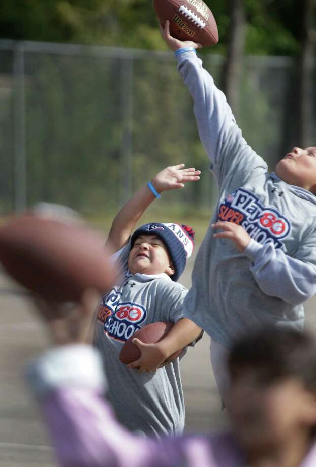 Jayden Woods, left, 9, a fourth grader and Nathan Rangel, 10, a third grader, at Briarmeadow Charter School, jump to catch a football thrown by Houston Texans player J.J. Watt during his visit at their school. Photo: Melissa Phillip, Houston Chronicle / © 2012 Houston Chronicle