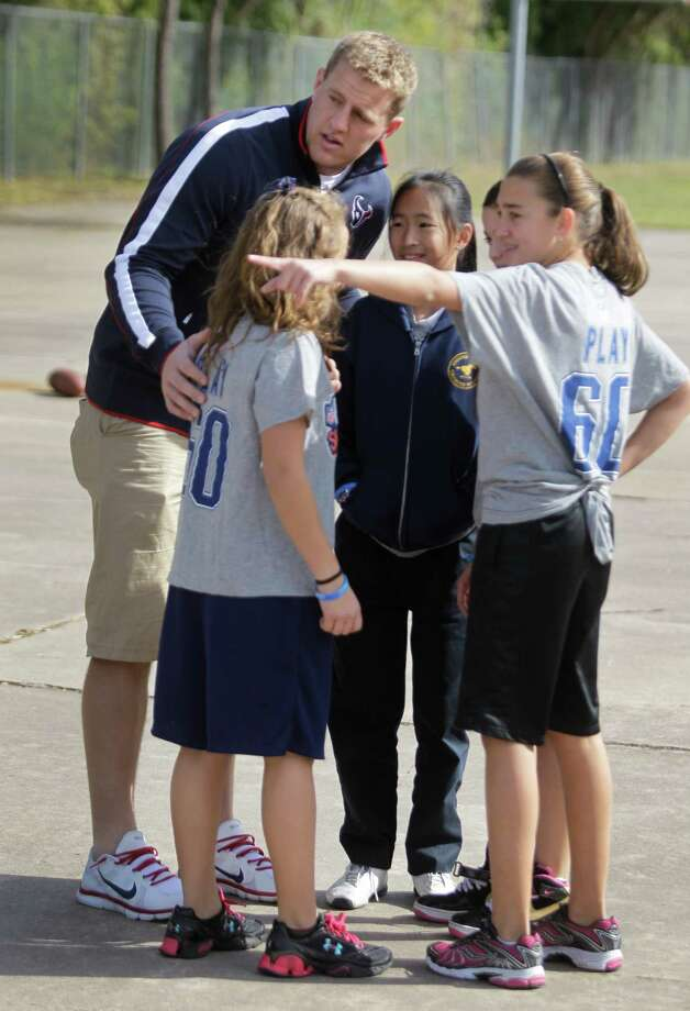 Houston Texans player J.J. Watt  huddles with Dominique Webb, left, Jacalyn Chen, Nicole Sagarra, and Alina Mooradian, right, all 11-year-old 6th graders, as they play at Briarmeadow Charter School. Photo: Melissa Phillip, Houston Chronicle / © 2012 Houston Chronicle