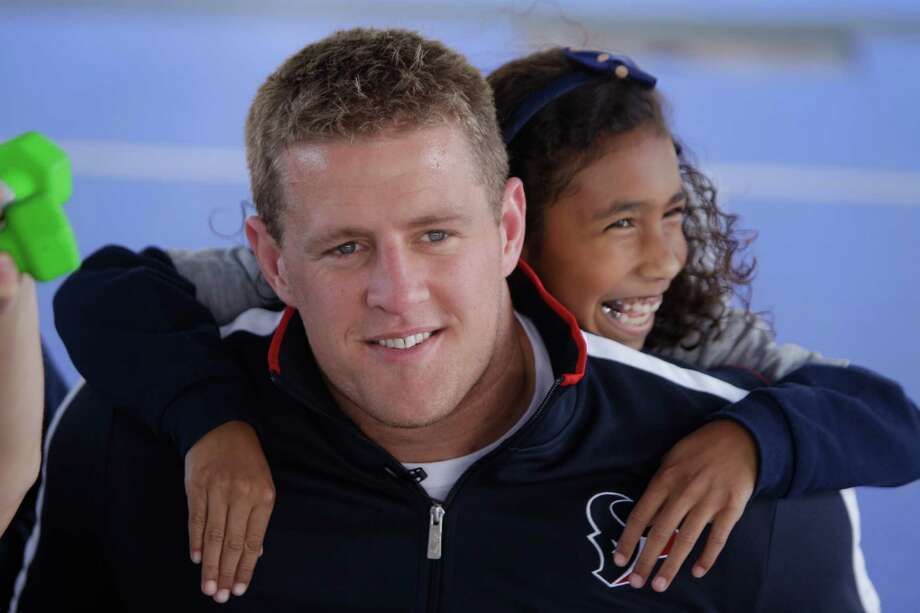 Houston Texans player J.J. Watt  is hugged by Lauren Parks, 8, a third grader at Briarmeadow Charter School, as she has her photo taken during his visit at their school Tuesday, Nov. 13, 2012, in Houston. Photo: Melissa Phillip, Houston Chronicle / © 2012 Houston Chronicle