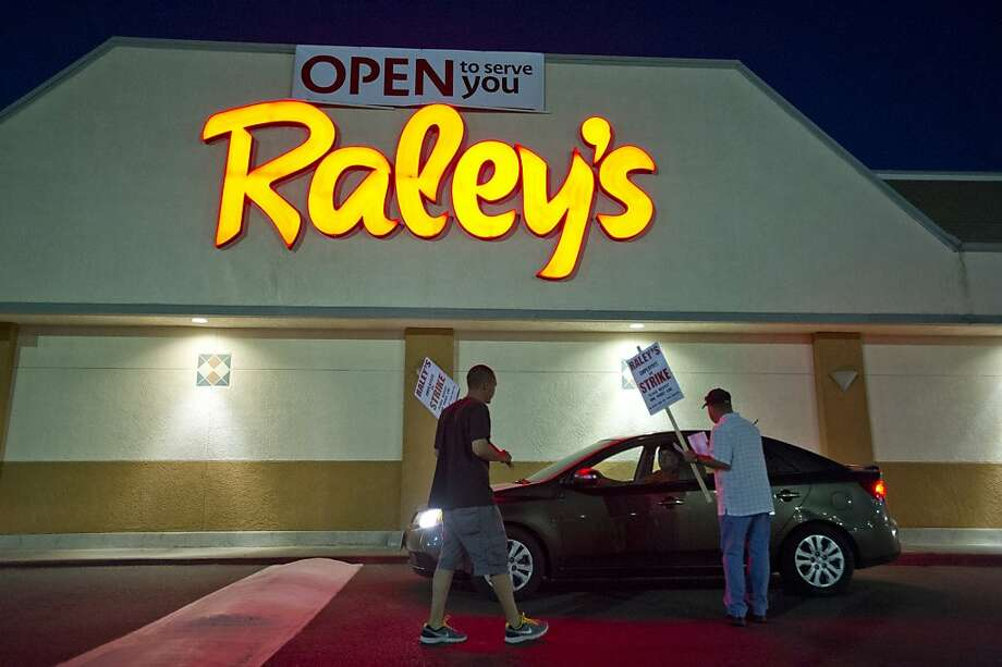 Dennis Robinson (right) hands out a flyer at the Raley's store in Sacramento. Photo: Paul Kitagaki Jr., Associated Press