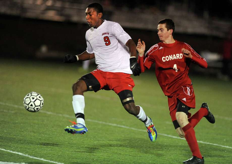 Fairfield Prep's Austin Sims gets ready to kick the ball for a game-winning goal as Conard's Michael D'Arcy defends during overtime in the Class LL soccer quarterfinals Tuesday, Nov. 13, 2012 at Alumni Field on the campus of Fairfield University. Photo: Autumn Driscoll / Connecticut Post