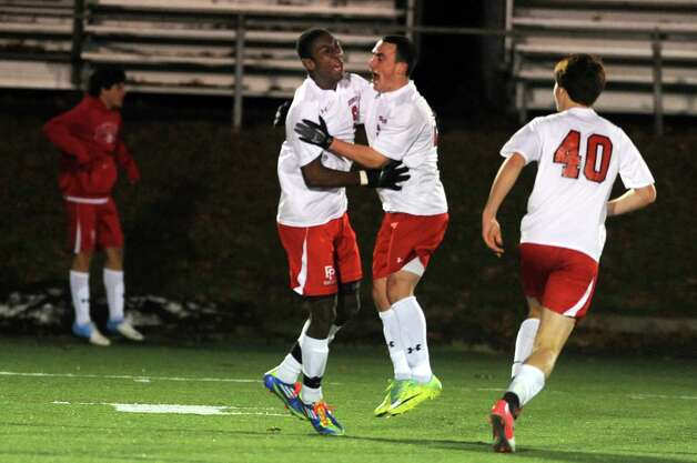Fairfield Prep's Austin Sims, left, celebrates his game-winning goal during overtime in the Class LL soccer quarterfinals against Conard Tuesday, Nov. 13, 2012 at Alumni Field on the campus of Fairfield University. Photo: Autumn Driscoll / Connecticut Post