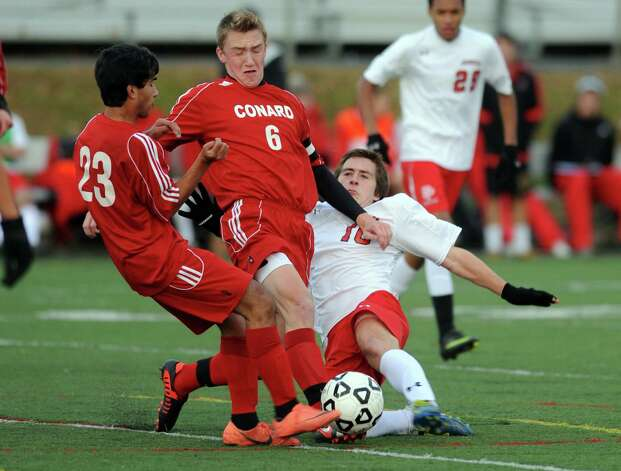 Fairfield Prep's David Bruton collides with Conard's Suyash Adhikari, left, and Christopher Warrren during the Class LL soccer quarterfinals Tuesday, Nov. 13, 2012 at Alumni Field on the campus of Fairfield University. Photo: Autumn Driscoll / Connecticut Post