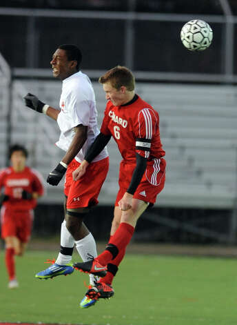 Fairfield Prep's Austin Sims heads the ball as Conard's Christopher Warren defends during overtime in the Class LL soccer quarterfinals Tuesday, Nov. 13, 2012 at Alumni Field on the campus of Fairfield University. Photo: Autumn Driscoll / Connecticut Post