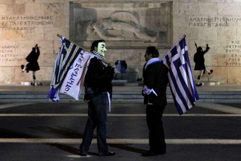 FILE - In this Sunday Nov. 11, 2012, file photo, supporters from the Independent Greeks party hold Greek flags as Presidential guards performs the changing of the guards ceremony outside the Greek parliament during an anti- austerity rally in central Athens. Stocks are opening lower on Wall Street  Tuesday, Nov. 13, 2012, as a deal to rescue the Greek economy now looks much less certain than it had just one day ago. (AP Photo/Petros Giannakouris, File) Photo: Petros Giannakouris