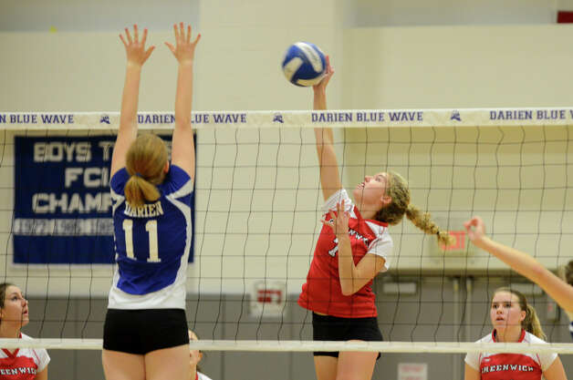 Greenwich's Liza Johnson (7) hits the ball over the net as Darien's Claire Naughton (11) defends during the girls volleyball match at Darien High School on Tuesday, Nov. 13, 2012. Photo: Amy Mortensen / Connecticut Post Freelance