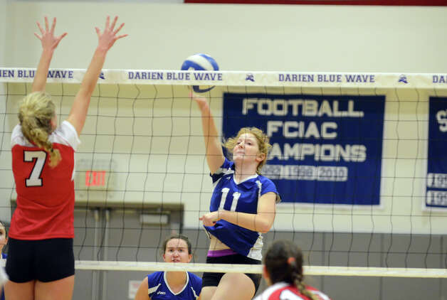 Darien's Claire Naughton (11) sends a shot over the net as Greenwich's Liza Johnson (7) defends during the girls volleyball match at Darien High School on Tuesday, Nov. 13, 2012. Photo: Amy Mortensen / Connecticut Post Freelance