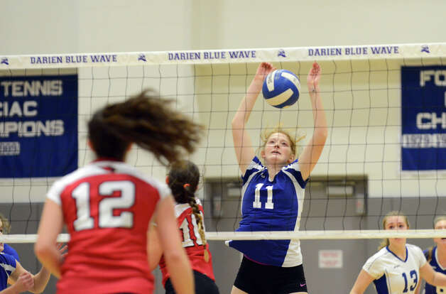 Darien's Claire Naughton (11) sends a shot over the net as Greenwich defends during the girls volleyball match at Darien High School on Tuesday, Nov. 13, 2012. Photo: Amy Mortensen / Connecticut Post Freelance