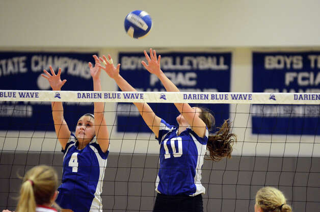 Darien's Lauren Pryor (4) and Taylor Cockerill (10) attempt to block a shot by Greenwich during the girls volleyball match at Darien High School on Tuesday, Nov. 13, 2012. Photo: Amy Mortensen / Connecticut Post Freelance